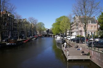 AMSTERDAM, NETHERLANDS, APRIL 20: People enjoy the sun on a wooden deck at a deserted Brouwersgracht amid the coronavirus outbreak on April 20, 2020 in Amsterdam, Netherlands. The city is unusually quiet due to the worldwide coronavirus (COVID-19) pandemic, which causes tourists to stay away. (Photo by Henk Seppen/BSR Agency/Getty Images)