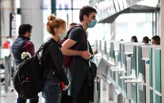 Passengers wearing a respiratory mask wait for check-in at the Terminal T1 of Rome's Fiumicino international airport on March 13, 2020. - Rome's Ciampino airport will shut to passenger flights from March 13, authorities said, with a Terminal T1 also closing at the city's main Fiumicino facility next week as airlines slash flights to Italy over the coronavirus outbreak. (Photo by Andreas SOLARO / AFP) (Photo by ANDREAS SOLARO/AFP via Getty Images)