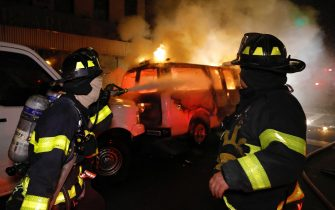 epa08455400 New York City firefighters spray water on a police van set ablaze by protesters during protests over the Minneapolis arrest of George Floyd, who later died in police custody, in Harlem, New York, USA, 30 May 2020. A bystander's video posted online on 25 May, appeared to show George Floyd, 46, pleading with arresting officers that he couldn't breathe as an officer knelt on his neck. The unarmed Black man later died in police custody. On 29 May, Derek Chauvin, the police officer in the center of the incident has been taken into costody and charged with murder in the Floyd arrest.  EPA/PETER FOLEY