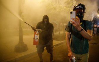 epa08455497 A demonstrator (L) sprays a fire extinguisher during protests over the Minneapolis arrest of George Floyd, who later died in police custody, near the White House in Washington, DC, USA, 30 May 2020. A bystander's video posted online on 25 May, appeared to show George Floyd, 46, pleading with arresting officers that he couldn't breathe as an officer knelt on his neck. The unarmed black man later died in police custody.  EPA/SHAWN THEW
