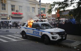 epa08455205 A New York City Police Department vehicle burns after being set alight by protesters as they demostrate about the arrest of George Floyd, who later died in police custody, in Brooklyn, New York, USA, 30 May 2020. A bystander's video posted online on 25 May, appeared to show George Floyd, 46, pleading with arresting officers that he couldn't breathe as an officer knelt on his neck. The unarmed black man later died in police custody.  EPA/KEVIN HAGEN