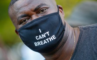 epa08455189 A protester wears a mask reading 'I can't breathe' during scuffles with US Park Police officers during protests over the Minneapolis arrest of George Floyd, who later died in police custody, near the White House in Washington, DC, USA, 30 May 2020. A bystander's video posted online on 25 May, appeared to show George Floyd, 46, pleading with arresting officers that he couldn't breathe as an officer knelt on his neck. The unarmed black man later died in police custody.  EPA/SHAWN THEW