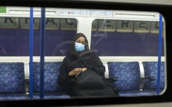 LONDON, ENGLAND - JUNE 01: A woman wearing a face mask sleeps on the underground under a sign that reads 'Knackered' on June 01, 2020 in London, England. The British government further relaxed Covid-19 quarantine measures in England this week, allowing groups of six people from different households to meet in parks and gardens, subject to social distancing rules. Many schools also reopened and vulnerable people who are shielding in their homes are allowed to go outside again. (Photo by Dan Kitwood/Getty Images)