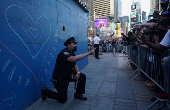 A New York City police officer takes a knee during a demonstration by protesters in Times Square over the death of George Floyd by a Minneapolis police officer at a rally on May 31, 2020 in New York. - Thousands of National Guard troops patrolled major US cities  after five consecutive nights of protests over racism and police brutality that boiled over into arson and looting, sending shock waves through the country. The death Monday of an unarmed black man, George Floyd, at the hands of police in Minneapolis ignited this latest wave of outrage in the US over law enforcement's repeated use of lethal force against African Americans -- this one like others before captured on cellphone video. (Photo by Bryan R. Smith / AFP)