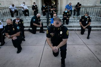 """TOPSHOT - Police officers kneel during a rally in Coral Gables, Florida on May 30, 2020 in response to the recent death of George Floyd, an unarmed black man who died while being arrested and pinned to the ground by a Minneapolis police officer. - Clashes broke out and major cities imposed curfews as America began another night of unrest Saturday with angry demonstrators ignoring warnings from President Donald Trump that his government would stop violent protests over police brutality """"cold."""" (Photo by Eva Marie UZCATEGUI / AFP)"""