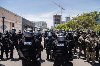 San Diego Police officers (L) in riot gear and a special tactics group (R) face-off with demonstrators in downtown San Diego, California on May 31, 2020, as people gather to protest against the death of Minneapolis man George Floyd. - Numerous cities across the US saw another day of violent protests after Floyd, an African-American, died on May 25 after being handcuffed and as a white police officer, who has since been charged with murder, knelt on his neck. (Photo by ARIANA DREHSLER / AFP) (Photo by ARIANA DREHSLER/AFP via Getty Images)