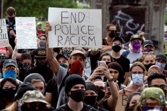 A demonstrator holds up a sign during a protest in Denver, Colorado on May 31, 2020, while protesting the death of George Floyd, an unarmed black man who died while while being arrested and pinned to the ground by the knee of a Minneapolis police officer. - Thousands of National Guard troops patrolled major US cities  after five consecutive nights of protests over racism and police brutality that boiled over into arson and looting, sending shock waves through the country. The death Monday of an unarmed black man, George Floyd, at the hands of police in Minneapolis ignited this latest wave of outrage in the US over law enforcement's repeated use of lethal force against African Americans -- this one like others before captured on cellphone video. (Photo by Jason Connolly / AFP) (Photo by JASON CONNOLLY/AFP via Getty Images)