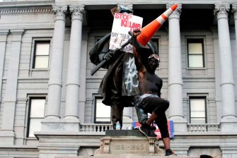 A demonstrator stands on a Civil War statue in Denver, Colorado on May 31, 2020, while protesting the death of George Floyd, an unarmed black man who died while while being arrested and pinned to the ground by the knee of a Minneapolis police officer. - Thousands of National Guard troops patrolled major US cities  after five consecutive nights of protests over racism and police brutality that boiled over into arson and looting, sending shock waves through the country. The death Monday of an unarmed black man, George Floyd, at the hands of police in Minneapolis ignited this latest wave of outrage in the US over law enforcement's repeated use of lethal force against African Americans -- this one like others before captured on cellphone video. (Photo by Jason Connolly / AFP) (Photo by JASON CONNOLLY/AFP via Getty Images)