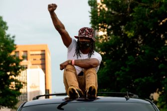 A demonstrator raises his fist while riding on top of a vehicle in Denver, Colorado on May 31, 2020, while protesting the death of George Floyd, an unarmed black man who died while while being arrested and pinned to the ground by the knee of a Minneapolis police officer. - Thousands of National Guard troops patrolled major US cities  after five consecutive nights of protests over racism and police brutality that boiled over into arson and looting, sending shock waves through the country. The death Monday of an unarmed black man, George Floyd, at the hands of police in Minneapolis ignited this latest wave of outrage in the US over law enforcement's repeated use of lethal force against African Americans -- this one like others before captured on cellphone video. (Photo by Jason Connolly / AFP) (Photo by JASON CONNOLLY/AFP via Getty Images)