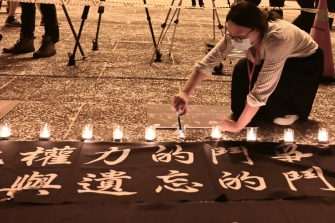 A woman lights candles in front of the Chiang Kai-shek Memorial Hall, also known as Free Square, to mark the 31st anniversary of the 1989 Tiananmen Square crackdown in Taipei in June 4, 2020. (Photo by Sam Yeh / AFP) (Photo by SAM YEH/AFP via Getty Images)
