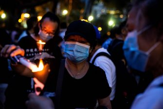 Activists light candles during a remembrance gathering outside Victoria Park in Hong Kong on June 4, 2020, after an annual vigil that traditionally takes place in the park to mark the 1989 Tiananmen Square crackdown was banned on public health grounds because of the COVID-19 coronavirus pandemic. (Photo by ISAAC LAWRENCE / AFP) (Photo by ISAAC LAWRENCE/AFP via Getty Images)