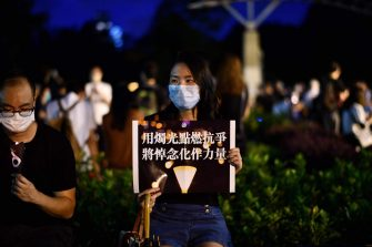 An activist holds a placard during a candlelit remembrance outside Victoria Park in Hong Kong on June 4, 2020, after an annual vigil that traditionally takes place in the park to mark the 1989 Tiananmen Square crackdown was banned on public health grounds because of the COVID-19 coronavirus pandemic. (Photo by Anthony WALLACE / AFP) (Photo by ANTHONY WALLACE/AFP via Getty Images)