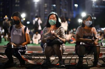 Activists hold a candlelit remembrance outside Victoria Park in Hong Kong on June 4, 2020, after an annual vigil that traditionally takes place in the park to mark the 1989 Tiananmen Square crackdown was banned on public health grounds because of the COVID-19 coronavirus pandemic. (Photo by Anthony WALLACE / AFP) (Photo by ANTHONY WALLACE/AFP via Getty Images)
