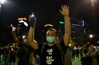 An activist, holding up a lit phone while gesturing the five demands of Hong Kong's pro-democracy protest movement, takes part in a candlelit remembrance outside Victoria Park in Hong Kong on June 4, 2020, after an annual vigil that traditionally takes place in the park to mark the 1989 Tiananmen Square crackdown was banned on public health grounds because of the COVID-19 coronavirus pandemic. (Photo by Anthony WALLACE / AFP) (Photo by ANTHONY WALLACE/AFP via Getty Images)