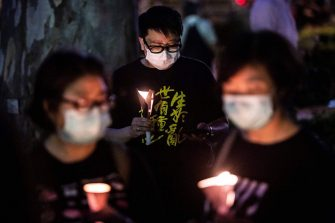 Activists hold a candlelit remembrance outside Victoria Park in Hong Kong on June 4, 2020, after an annual vigil that traditionally takes place in the park to mark the 1989 Tiananmen Square crackdown was banned on public health grounds because of the COVID-19 coronavirus pandemic. (Photo by ISAAC LAWRENCE / AFP) (Photo by ISAAC LAWRENCE/AFP via Getty Images)