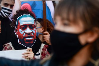 BUENOS AIRES, ARGENTINA - JUNE 02: A protester holds a sign with a picture of George Floyd during a demonstration on June 2, 2020 in Buenos Aires, Argentina. Protests spread across cities around the world in response to the death of African American George Floyd while in police custody in Minneapolis, Minnesota. (Photo by Gustavo Garello/Jam Media/Getty Images)