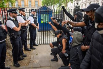 LONDON, ENGLAND - JUNE 03: People kneel in front of police during a Black Lives Matter protest at Hyde Park on June 03, 2020 in London, England.  The death of an African-American man, George Floyd, while in the custody of Minneapolis police has sparked protests across the United States, as well as demonstrations of solidarity in many countries around the world. (Photo by Justin Setterfield/Getty Images)