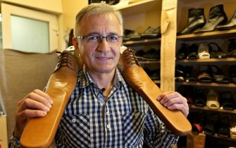 epa08466353 Romanian shoemaker Grigore Lup poses with a pair of men's social-distancing shoes, measuring 0.75 meters, at his workshop, in Cluj Napoca city, 500 kms north-west of Bucharest, Romania, 04 June 2020 (issued 05 June 2020). Lup, 55, invented the social distancing shoes in a bid to save his small business in the midst of the Coronavirus crisis. The shoemaker is manufacturing by hand each pair of social distancing shoes, using the best natural leather, hand tools plus his 39 years professional experience. After receiving attention from the local media, he began to receive orders from around the world. Most of his customers are confessing that they want to wear his creations on the street or at special occasions. The master shoemaker, who managed to survive the global financial crisis of 2008 by moving from normal shoes to the production of footwear for dance companies and theaters, turned the disadvantage of the Covid-19 pandemic in his favor, producing social distance shoes for both men and women. He is selling a pair of his special shoes for about 100 euros.  EPA/Alexandru Pop To go with the story: 'Number 75 shoes to enforce social distance' by Marcel Gascon/EFE