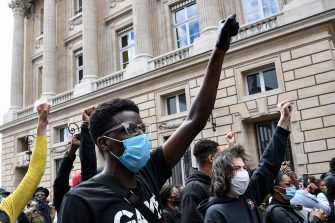 Demonstrators raise a fist during a rally near the place de la Concorde and the US embassy compound, in Paris on June 6, 2020, as part of a weekend of global rallies worldwide against racism and police brutality in the wake of the death of George Floyd, an unarmed black man killed while apprehended by police in Minneapolis, US. - Police banned the rally as well as a similar second one on the Champs de Mars park facing the Eiffel Tower today, saying the events were organised via social networks without official notice or consultation. But on June 2, another banned rally in Paris drew more than 20000 people in support of the family of Adama Traore, a young black man who died in police custody in 2016. (Photo by Anne-Christine POUJOULAT / AFP)
