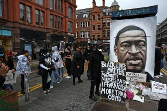 """Protesters place their placards at the base of a mural of George Floyd, by street artist Akse, following a demonstration in Manchester, northern England, on June 6, 2020, to show solidarity with the Black Lives Matter movement in the wake of the killing of George Floyd, an unarmed black man who died after a police officer knelt on his neck in Minneapolis. - The United States braced Friday for massive weekend protests against racism and police brutality, as outrage soared over the latest law enforcement abuses against demonstrators that were caught on camera. With protests over last week's police killing of George Floyd, an unarmed black man, surging into a second weekend, President Donald Trump sparked fresh controversy by saying it was a """"great day"""" for Floyd. (Photo by Paul ELLIS / AFP) / RESTRICTED TO EDITORIAL USE - MANDATORY MENTION OF THE ARTIST UPON PUBLICATION - TO ILLUSTRATE THE EVENT AS SPECIFIED IN THE CAPTION"""