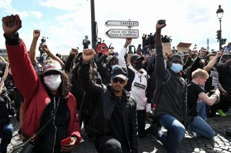 People kneel and raise a fist on the place de la Concorde near the US embassy compound, in Paris on June 6, 2020, as part of 'Black Lives Matter' worldwide protests against racism and police brutality in the wake of the death of George Floyd, an unarmed black man killed while apprehended by police in Minneapolis, US. - Police banned the rally as well as a similar second one on the Champs de Mars park facing the Eiffel Tower today, saying the events were organised via social networks without official notice or consultation. But on June 2, another banned rally in Paris drew more than 20000 people in support of the family of Adama Traore, a young black man who died in police custody in 2016. (Photo by Anne-Christine POUJOULAT / AFP)