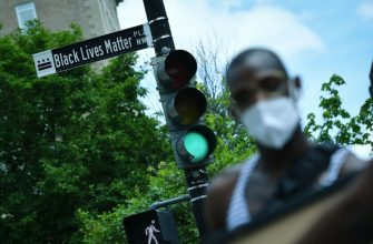 """A woman is seen in front of a street sign for the newly proclaimed """"Black Lives Matter Plaza"""" near the White House in Washington, DC, on June 5 2020. (Photo by MANDEL NGAN / AFP) (Photo by MANDEL NGAN/AFP via Getty Images)"""