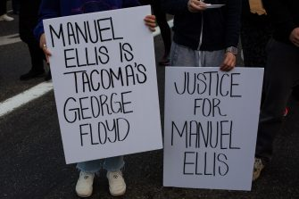 TACOMA, WA - JUNE 03: People hold signs during a vigil for Manuel Ellis, a black man whose March death while in Tacoma Police custody was recently found to be a homicide, according to the Pierce County Medical Examiners Office, near the site of his death on June 3, 2020 in Tacoma, Washington. Protests and other events sparked by the death of George Floyd have continued in the Tacoma area after the Medical Examiner found that the cause of death in the Manuel Ellis case was caused by respiratory arrest due to hypoxia due to physical restraint. (Photo by David Ryder/Getty Images)