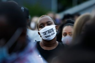 """A man attending a vigil wears a mask with the words """"I can't breathe"""" and the name of Manuel Ellis a 33-year-old black man who died in Tacoma Police custody on March 3 and was recently ruled a homicide, according to the Pierce County Medical Examiners Office, in Tacoma, Washington on June 3, 2020. - US protesters welcomed new charges brought Wednesday against Minneapolis officers in the killing of African American man George Floyd -- but thousands still marched in cities across the country for a ninth straight night, chanting against racism and police brutality. (Photo by Jason Redmond / AFP) (Photo by JASON REDMOND/AFP via Getty Images)"""