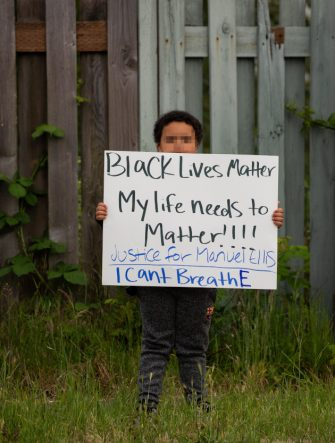 TACOMA, WA - JUNE 03: A boy holds a sign during a vigil for Manuel Ellis, a black man whose March death while in Tacoma Police custody was recently found to be a homicide, according to the Pierce County Medical Examiners Office, near the site of his death on June 3, 2020 in Tacoma, Washington. Protests and other events sparked by the death of George Floyd have continued in the Tacoma area after the Medical Examiner found that the cause of death in the Manuel Ellis case was caused by respiratory arrest due to hypoxia due to physical restraint. (Photo by David Ryder/Getty Images)
