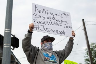 TACOMA, WA - JUNE 03: Brian Giordano holds a sign during a vigil for his best friend, Manuel Ellis, a black man whose March death while in Tacoma Police custody was recently found to be a homicide, according to the Pierce County Medical Examiners Office, near the site of his death on June 3, 2020 in Tacoma, Washington. Protests and other events sparked by the death of George Floyd have continued in the Tacoma area after the Medical Examiner found that the cause of death in the Manuel Ellis case was caused by respiratory arrest due to hypoxia due to physical restraint. (Photo by David Ryder/Getty Images)