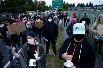 Family, friends and community members attend a vigil at the intersection where Manuel Ellis, a 33-year-old black man, died in Tacoma Police custody on March 3 and was recently ruled a homicide, according to the Pierce County Medical Examiners Office, in Tacoma, Washington on June 3, 2020. - US protesters welcomed new charges brought Wednesday against Minneapolis officers in the killing of African American man George Floyd -- but thousands still marched in cities across the country for a ninth straight night, chanting against racism and police brutality. (Photo by Jason Redmond / AFP) (Photo by JASON REDMOND/AFP via Getty Images)