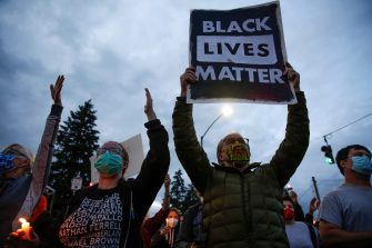A man holds a black lives matter sign as family, friends and community members attend a vigil at the intersection where Manuel Ellis, a 33-year-old black man, died in Tacoma Police custody on March 3 and was recently ruled a homicide, according to the Pierce County Medical Examiners Office, in Tacoma, Washington on June 3, 2020. - US protesters welcomed new charges brought Wednesday against Minneapolis officers in the killing of African American man George Floyd -- but thousands still marched in cities across the country for a ninth straight night, chanting against racism and police brutality. (Photo by Jason Redmond / AFP) (Photo by JASON REDMOND/AFP via Getty Images)