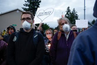 """A woman holds a """"stronger together"""" sign as family, friends and community members attend a vigil at the intersection where Manuel Ellis, a 33-year-old black man, died in Tacoma Police custody on March 3 and was recently ruled a homicide, according to the Pierce County Medical Examiners Office, in Tacoma, Washington on June 3, 2020. - US protesters welcomed new charges brought Wednesday against Minneapolis officers in the killing of African American man George Floyd -- but thousands still marched in cities across the country for a ninth straight night, chanting against racism and police brutality. (Photo by Jason Redmond / AFP) (Photo by JASON REDMOND/AFP via Getty Images)"""