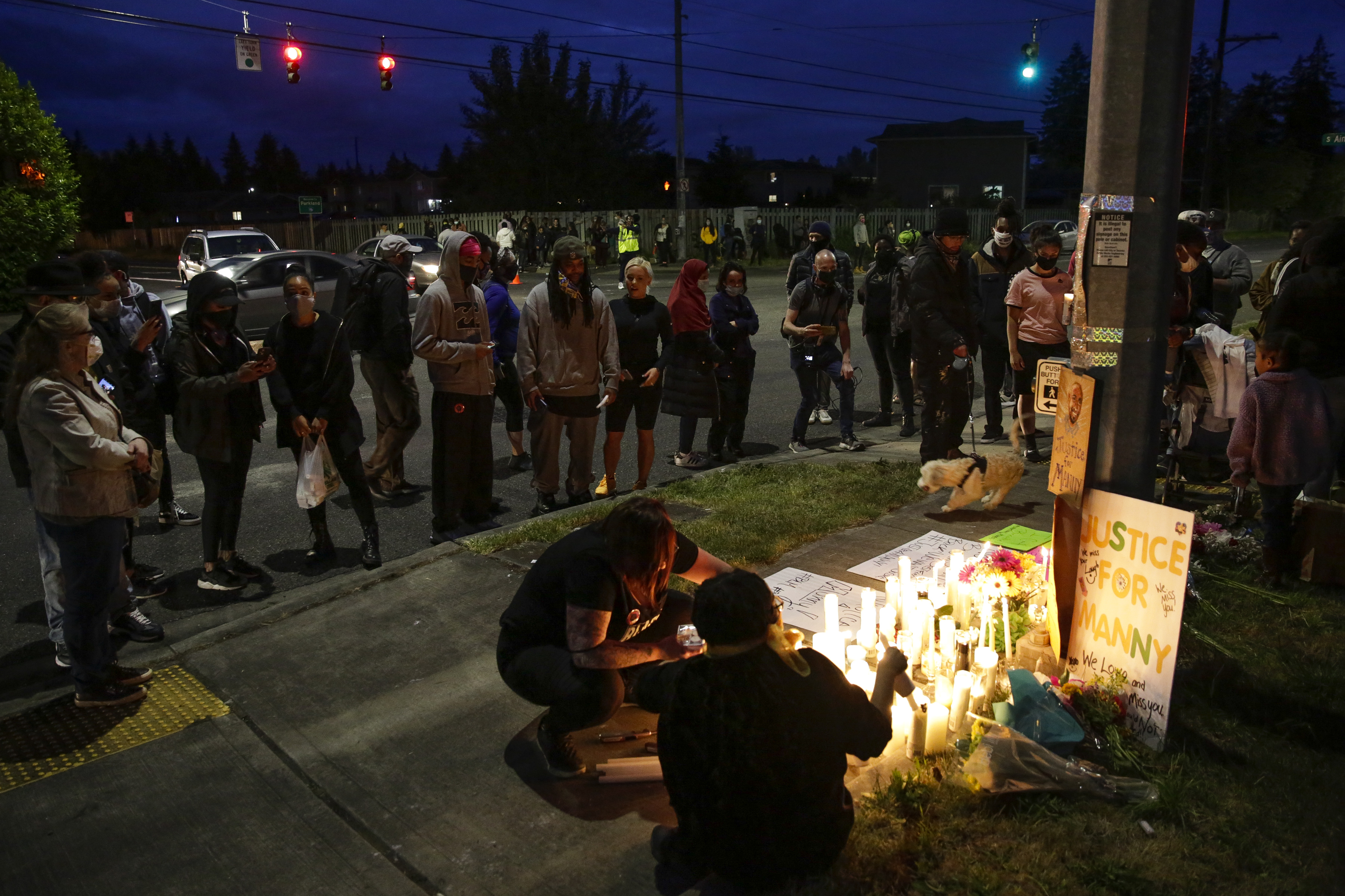 People gather and light candles at a makeshift memorial at the intersection where Manuel Ellis, a 33-year-old black man, died in Tacoma Police custody on March 3 and was recently ruled a homicide, according to the Pierce County Medical Examiners Office, in Tacoma, Washington on June 3, 2020. - US protesters welcomed new charges brought June 3 against Minneapolis officers in the killing of African American man George Floyd -- but thousands still marched in cities across the country for a ninth straight night, chanting against racism and police brutality. (Photo by Jason Redmond / AFP) (Photo by JASON REDMOND/AFP via Getty Images)