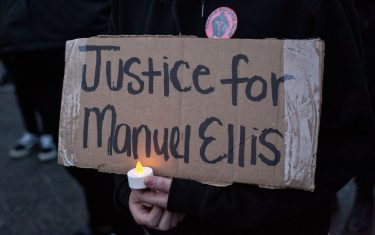 TACOMA, WA - JUNE 03: A person holds a sign during a vigil for Manuel Ellis, a black man whose March death while in Tacoma Police custody was recently found to be a homicide, according to the Pierce County Medical Examiners Office, near the site of his death on June 3, 2020 in Tacoma, Washington. Protests and other events sparked by the death of George Floyd have continued in the Tacoma area after the Medical Examiner found that the cause of death in the Manuel Ellis case was caused by respiratory arrest due to hypoxia due to physical restraint. (Photo by David Ryder/Getty Images)