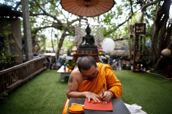 epa08470616 A Thai Buddhist monk inscribes with spiritual incantations aimed to protect devotees from the fear of the COVID-19 disease and coronavirus pandemic on a facial mask made from recycled plastic bottles at Wat Chak Daeng temple in Samut Prakan province, Thailand, 03 June 2020 (issued 07 June 2020). The Buddhist temple Wat Chak Daeng is well-known for managing the environmental campaign calling for donations of plastic bottles then transforming them into recycled fabrics before weaving and embroidering them into antibacterial robes. Amid the concerns of the ongoing spread of the COVID-19 disease, monks and volunteers produce facial mask made from used polyethylene terephthalate (PET) bottles collected by the temple's Buddhist monks, residents and donations aimed to control plastic waste as part of a waste management project to support environment protection and enhancing economic opportunities through recycled products. Thailand is one of the world's largest plastic polluters by generating more than two million tons of plastic waste each year.  EPA/RUNGROJ YONGRIT