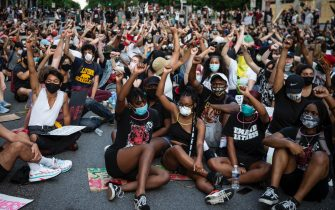 epa08470463 People sit and raise their fist in protest near the White House, where there has been a week of protests over the death of George Floyd, who died in police custody, in Washington, DC, USA, 06 June 2020. Cities across the United States are expecting large protests over the death of George Floyd. A bystander's video posted online on 25 May, appeared to show Floyd, 46, pleading with arresting officers that he couldn't breathe as an officer knelt on his neck. The unarmed black man later died in police custody.  EPA/SARAH SILBIGER