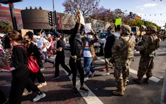 epa08470567 National Guard soldiers interact with protesters as they march during a demonstration as part of the continuing reaction to the death of George Floyd in Los Angeles, California, USA, 06 June 2020. A bystander's video posted online on 25 May, appeared to show George Floyd, 46, pleading with arresting officers that he couldn't breathe as an officer knelt on his neck. The unarmed black man later died in police custody.  EPA/ETIENNE LAURENT