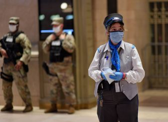 A customer service usher is waiting to hand out free face masks to commuters at Grand Central Station during morning rush hour on June 8, 2020 in New York City. (Photo by Angela Weiss / AFP) (Photo by ANGELA WEISS/AFP via Getty Images)