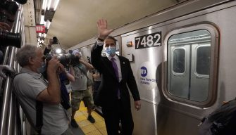 "New York Governor Andrew Cuomo waves after riding the New York City subway 7 train into the city on June 8, 2020 in New York. - Today New York City enters ""Phase 1"" of a four-part reopening plan after spending more than two months under lockdown. New York City is the final region in the state to reopen its economy. (Photo by TIMOTHY A. CLARY / AFP) (Photo by TIMOTHY A. CLARY/AFP via Getty Images)"