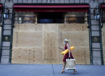 "A woman walks by a boarded up Cartier store on 5th Avenue in New York City June 8, 2020. - Today New York City enters ""Phase 1"" of a four-part reopening plan after spending more than two months under lockdown. New York City is the final region in the state to reopen its economy. (Photo by TIMOTHY A. CLARY / AFP) (Photo by TIMOTHY A. CLARY/AFP via Getty Images)"