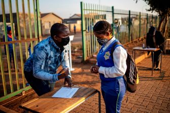 A teacher at the Winnie Mandela Secondary School asks screening question to a pupil before admitting her into the school premises as classes resume in the Tembisa township, Ekurhuleni, on June 8, 2020. - Grade 7 and grade 12 pupils in South Africa began returning to classrooms on June 8, 2020  after two and a half months of home-schooling to limit the spread of the COVID-19 coronavirus. (Photo by Michele Spatari / AFP) (Photo by MICHELE SPATARI/AFP via Getty Images)