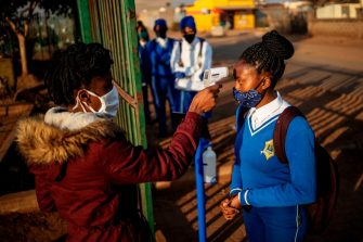 A pupil at the Winnie Mandela Secondary School has her temperature measured as she enters the school premises before classes resume in the Tembisa township, Ekurhuleni, on June 8, 2020. - Grade 7 and grade 12 pupils in South Africa began returning to classrooms on June 8, 2020  after two and a half months of home-schooling to limit the spread of the COVID-19 coronavirus. (Photo by Michele Spatari / AFP) (Photo by MICHELE SPATARI/AFP via Getty Images)