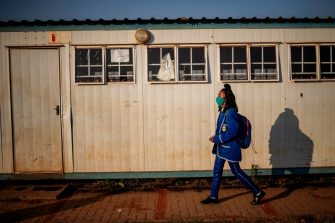 A pupil at the Winnie Mandela Secondary School walks past a closed classroom as classes resume in Tembisa township, Ekurhuleni, on June 8, 2020. - Grade 7 and grade 12 pupils in South Africa began returning to classrooms on June 8, 2020  after two and a half months of home-schooling to limit the spread of the COVID-19 coronavirus. (Photo by Michele Spatari / AFP) (Photo by MICHELE SPATARI/AFP via Getty Images)