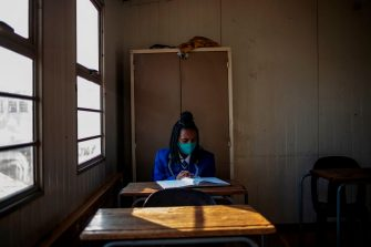 A pupil at the Winnie Mandela Secondary School studies at her desk as classes resume in Tembisa township, Ekurhuleni, on June 8, 2020. - Grade 7 and grade 12 pupils in South Africa began returning to classrooms on June 8, 2020  after two and a half months of home-schooling to limit the spread of the COVID-19 coronavirus. (Photo by Michele Spatari / AFP) (Photo by MICHELE SPATARI/AFP via Getty Images)