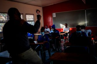 Pupils at the Winnie Mandela Secondary School listen to a teacher as classes resume in Tembisa township, Ekurhuleni, on June 8, 2020. - Grade 7 and grade 12 pupils in South Africa began returning to classrooms on June 8, 2020  after two and a half months of home-schooling to limit the spread of the COVID-19 coronavirus. (Photo by Michele Spatari / AFP) (Photo by MICHELE SPATARI/AFP via Getty Images)