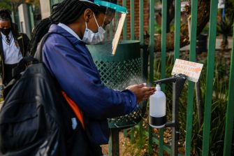 A pupil sanitises her hands before entering the school premises at the CR Swart High School in Pretoria on June 8, 2020. - Grade 7 and grade 12 pupils in South Africa began returning to classrooms on June 8, 2020  after two and a half months of home-schooling to limit the spread of the COVID-19 coronavirus. (Photo by Christiaan KOTZE / AFP) (Photo by CHRISTIAAN KOTZE/AFP via Getty Images)