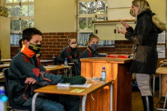 Pupils wear face masks inside their classroom while looking at a COVID-19 coronavirus awareness video at the Totiusdal Primary School in Pretoria on June 8, 2020. - Grade 7 and grade 12 pupils in South Africa began returning to classrooms on June 8, 2020  after two and a half months of home-schooling to limit the spread of the COVID-19 coronavirus. (Photo by Christiaan KOTZE / AFP) (Photo by CHRISTIAAN KOTZE/AFP via Getty Images)