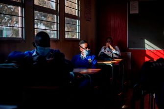 Pupils at the Winnie Mandela Secondary School listen to a teacher as classes resume in the Tembisa township, Ekurhuleni, on June 8, 2020. - Grade 7 and grade 12 pupils in South Africa began returning to classrooms on June 8, 2020  after two and a half months of home-schooling to limit the spread of the COVID-19 coronavirus. (Photo by Michele Spatari / AFP) (Photo by MICHELE SPATARI/AFP via Getty Images)