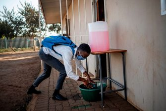 A pupil at the Winnie Mandela Secondary School sanitises his hands before entering a classroom as classes resume in the Tembisa township, Ekurhuleni, on June 8, 2020. - Grade 7 and grade 12 pupils in South Africa began returning to classrooms on June 8, 2020  after two and a half months of home-schooling to limit the spread of the COVID-19 coronavirus. (Photo by Michele Spatari / AFP) (Photo by MICHELE SPATARI/AFP via Getty Images)